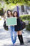 Excited Mixed Race Female Students Holding Blank Chalkboard Royalty Free Stock Photo