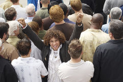 Excited Mixed Race Man Amid Rear View Of Multiethnic Crowd stock photo