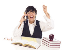Excited Mixed Race Teen Student on Cell Phone Cheers. Excited Mixed Race Female Student at Desk with Books on Cell Phone Cheers Isolated on a White Background Royalty Free Stock Photography