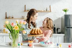Mother and child looking at each other near easter eggs, decorative rabbits, easter bread and tulips. Excited mother and child looking at each other near easter