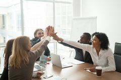 Excited motivated african and caucasian business team giving hig. Excited african and caucasian business team giving high five at office meeting motivated by stock photo