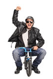 Excited motorcyclist riding a tiny bicycle Stock Photos