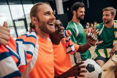 excited multicultural football fans in orange t-shirts and scarf celebrating victory with ball while their upset friends in royalty free stock image