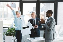 Excited multiethnic business people applauding and throwing papers. In office stock photography