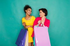 Excited multiethnic girls with shopping bags Royalty Free Stock Images