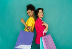 Excited multiethnic girls with shopping bags Stock Images