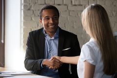 Excited partners handshake after successful interview in office. Excited multiracial business partners shake hand congratulate after successful negotiations royalty free stock photos
