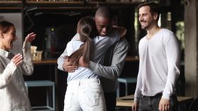 Excited multiracial friends greeting hugging mate at meeting in cafe. Excited multiracial friends greeting hugging female mate at reunion in cafe, happy diverse stock video