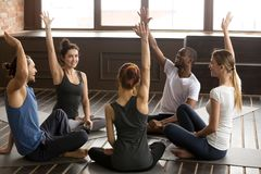 Excited multiracial people raising hands together at group yoga Stock Photography