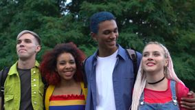 Excited multiracial students couples walking in park and smiling, friendship