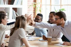 Excited multiracial team giving high five at company meeting. Excited happy multiracial team giving high five, celebrating good results, smiling African American royalty free stock photos