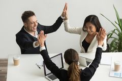 Excited multiracial team holding hands giving high five celebrat. Excited multiracial team giving high five together celebrating victory business success, happy royalty free stock photo