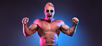 Excited Muscular strong athletic man naked torso. Excited Muscular strong expressive man with naked torso in fashion neon light. Sexy pumped-up bodybuilder stock images
