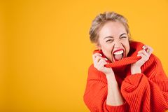 Excited naughty screaming blonde woman portrait in red jumper on vivid  yellow background. Horizontal photo