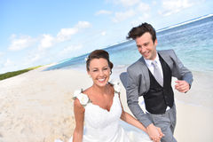 Excited newly-weds running on the beach. Just married couple running on a caribbean beach Royalty Free Stock Images