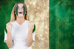 Excited nigeria fan in face paint cheering Stock Photo