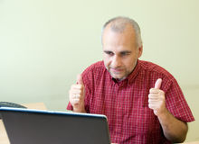 Excited office worker. Working at the desk with thumbs up stock photography
