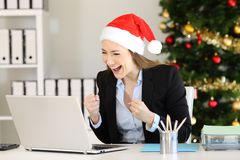 Excited office worker receiving good news in christmas. Excited office worker receiving good news on line in a laptop in christmas time stock images