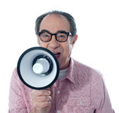 Excited old man making an announcement. Through megaphone, close to camera Royalty Free Stock Image