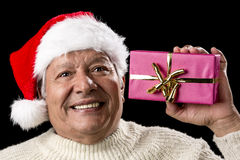 Excited Old Man With Santa Cap And Magenta Gift. Happy elderly gentleman with red Nicholas hat is raising a wrapped Christmas gift in his left hand. Golden Royalty Free Stock Photo