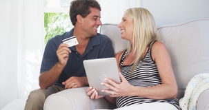 Excited parents smiling at camera with credit card Stock Images