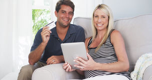 Excited parents smiling at camera with credit card Royalty Free Stock Photography