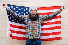 Excited patriot of American style. Excited young man holding American flag while standing against brick wall Royalty Free Stock Photo