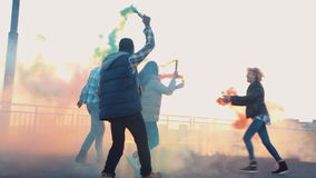 Excited people with colored smoke grenades