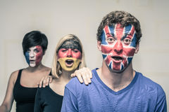 Excited people with European flags on faces. Group of exited people with painted flags on their faces shouting Royalty Free Stock Image