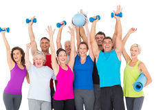 Excited people with exercise equipment raising hands. Portrait of excited people with exercise equipment raising hands against white background Stock Image