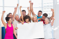 Excited people holding blank billboard at gym. Excited fit people holding blank billboard against window at gym Royalty Free Stock Images
