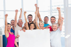 Excited people holding blank billboard. Portrait of excited fit people holding blank billboard at health club Stock Photos