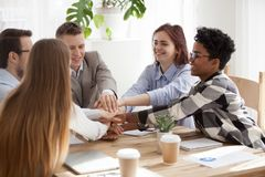 Excited people stacking hands sitting in office stock photos