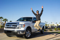 Excited Person Jumping for Joy. A young man is exited after buying his first truck Royalty Free Stock Photos