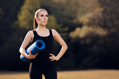 Excited Pilates Girl with Yoga Mat Standing Royalty Free Stock Photos