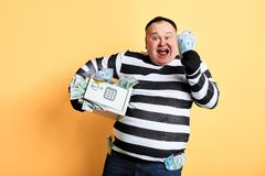 Excited plump man in striped uniform rejoicing at stolen money. Isolated yellow background royalty free stock photography