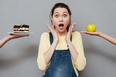 Excited pregnant woman choosing between apple and a cake Stock Photos