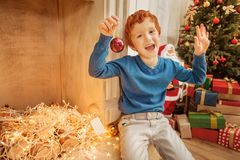 Excited preteen kid enjoying christmas preparation at home. Festive positivity. Extremely happy redhead boy gesturing while sitting at a fireplace and getting Stock Image