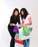 Excited preteens with shopping bags. Pretty brunette teen girls holding gift bags Royalty Free Stock Photo