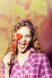 Excited pretty girl laughs with red heart on stick. Excited pretty girl or beautiful woman with blond hair in stylish headband and plaid shirt laughs with red royalty free stock photography