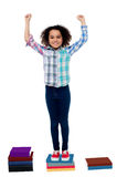 Excited pretty school child standing on books. Yippee I stood first in my class. Excited schoolgirl Stock Photos
