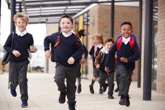 Excited primary school kids, wearing school uniforms and backpacks, running on a walkway outside their school building, front view. Close up stock image