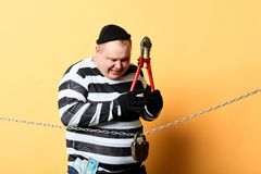 Excited prisoner using scissors to cut the chain. Excited prisoner in striped clothes using scissors to cut the chain. isolated yellow background. studio shot royalty free stock photography
