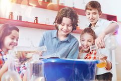 Excited pupils pouring different chemistry liquids into giant plastic bowl Stock Photos