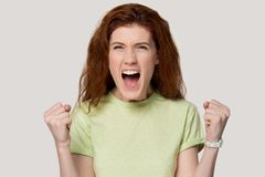 Excited red-haired girl scream with happiness about success. Excited young red-haired woman in casual clothes isolated on grey studio background scream with stock images