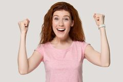 Excited redhead girl feel euphoric about success royalty free stock photography