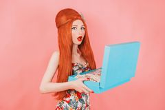 Excited redhead girl open a gift box for the holiday. Woman with long red hair in trendy summer dress with blue present box on pin. K background. Excited model royalty free stock image