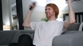 Excited redhead man reacting to success, watching tv. 4k , high quality stock video