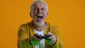 Excited retired male playing video game by joystick, modern technology, hobby. Stock footage stock footage