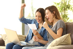 Excited roommates reading a bank notification Royalty Free Stock Photography